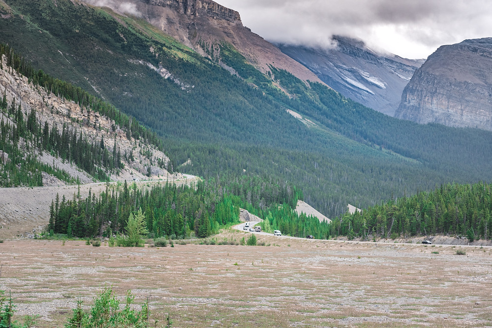 The Icefields Parkway surrounded by mountains under a stormy sky in Alberta, Canada.