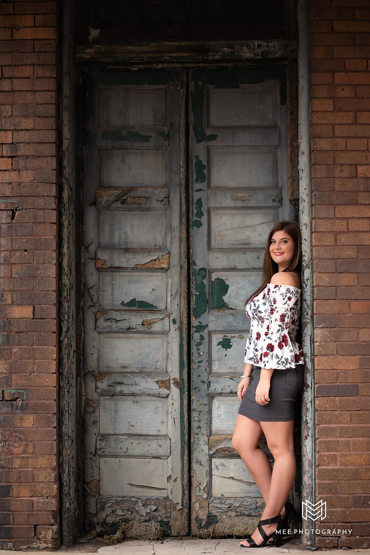 Senior girl standing in urban doorway during her senior pictures
