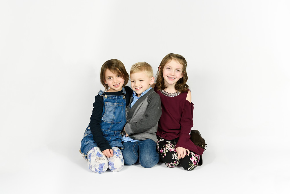 Two sisters and a brother posed smiling at the camera in front of a white backdrop during their photo session.
