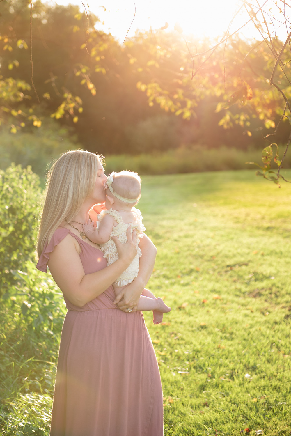 Mom kissing her baby girl in a field with brilliant sunlight behind her