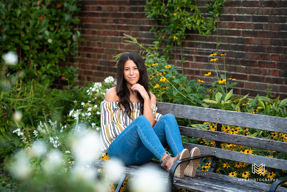 Senior photos of a girl wearing jeans surrounded by flowers at Mellon Park