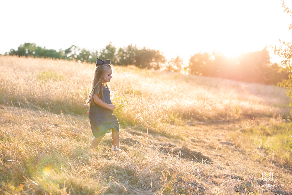 Young girl in a dress with a blue bow in her hair walking through a field at sunset in Chester, WV