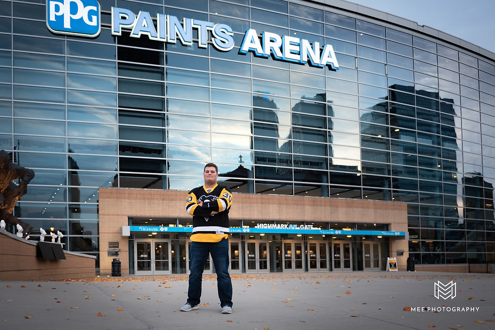 Senior guy wearing a Pittsburgh Penguins jersey standing in front of the PPG Paints arena