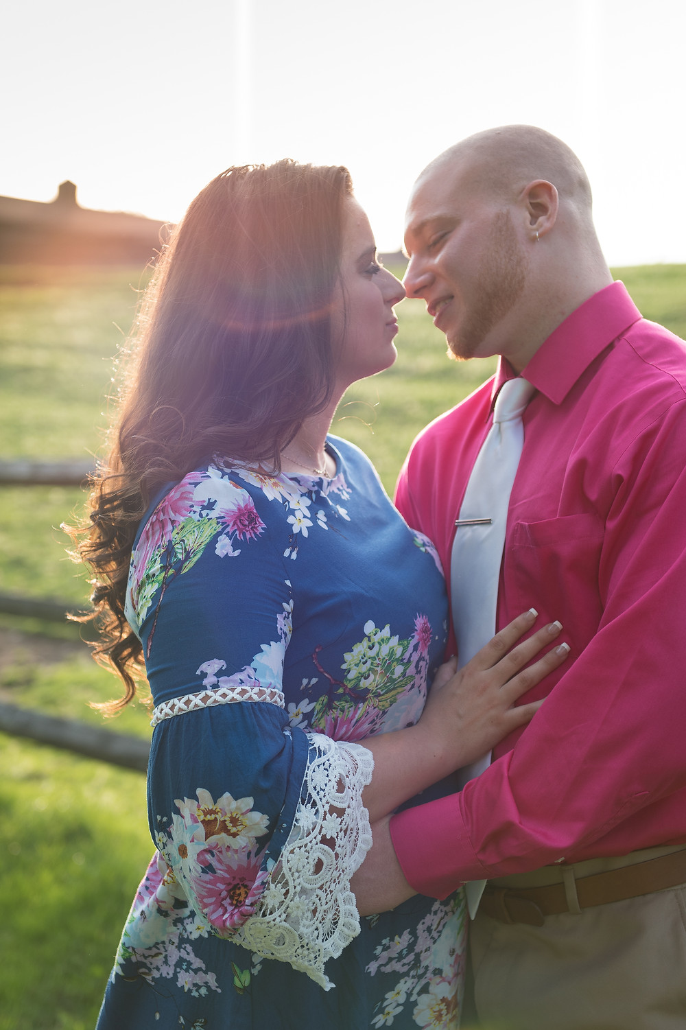 Couple leaning in for a kiss in front of a horse pasture at Oglebay. Woman is wearing a blue floral dress and man is wearing a pink dress shirt and silver tie.