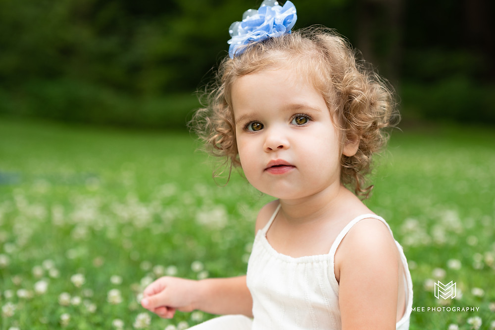 Two year old girl with curly hair sitting in the grass at Brady's Run