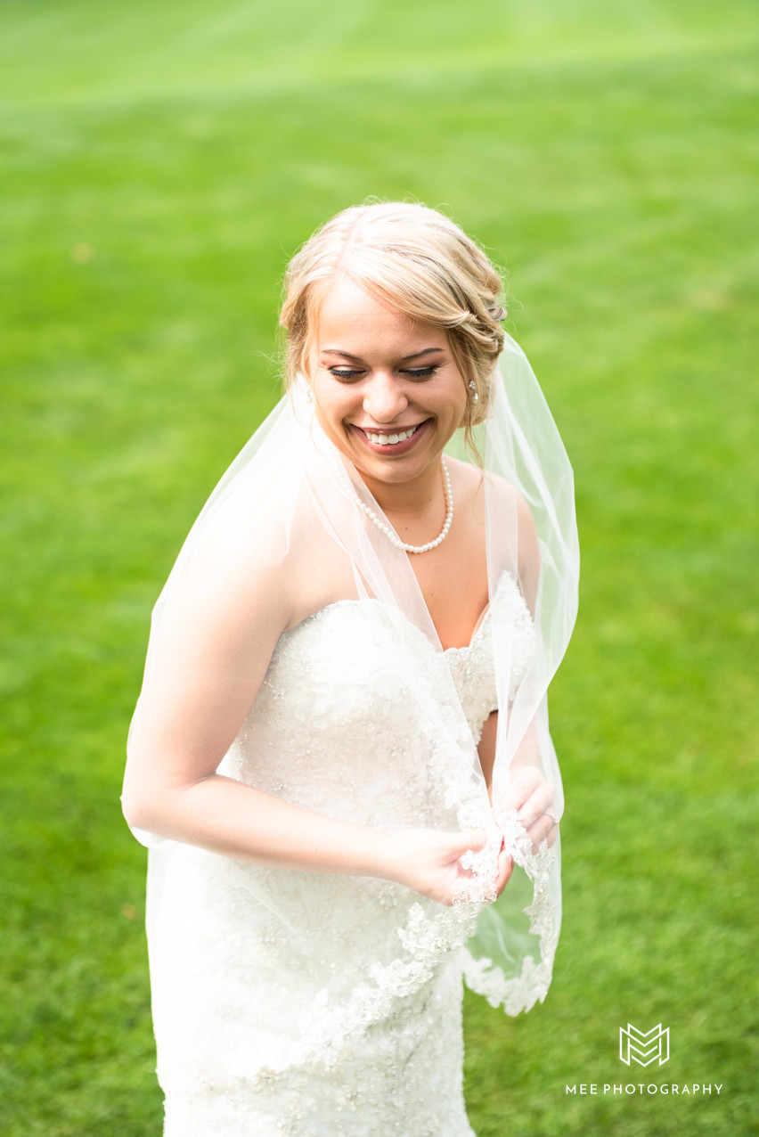 Bride posed holding veil and smiling towards the ground