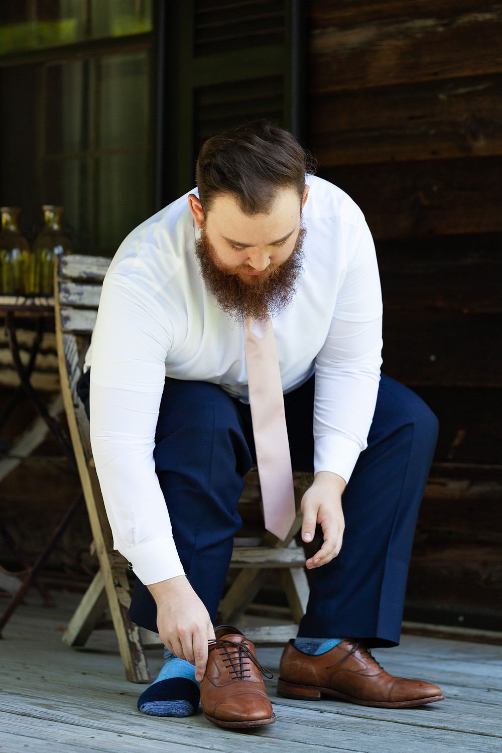 Groom putting his shoes on outside of the cabin at Chanteclaire Farm