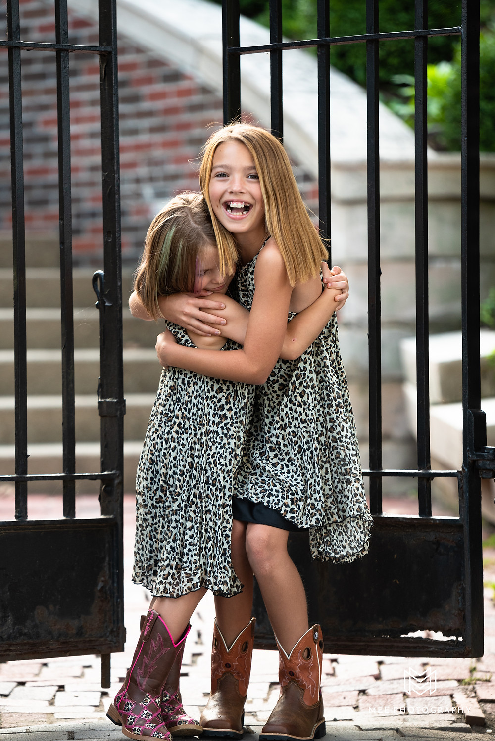 Sisters hugging and laughing in leopard print dresses in front of iron gates at Bethany College