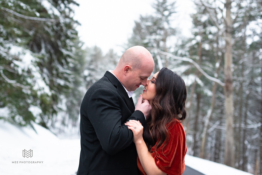 Engagement session with snow covered pine trees in the background