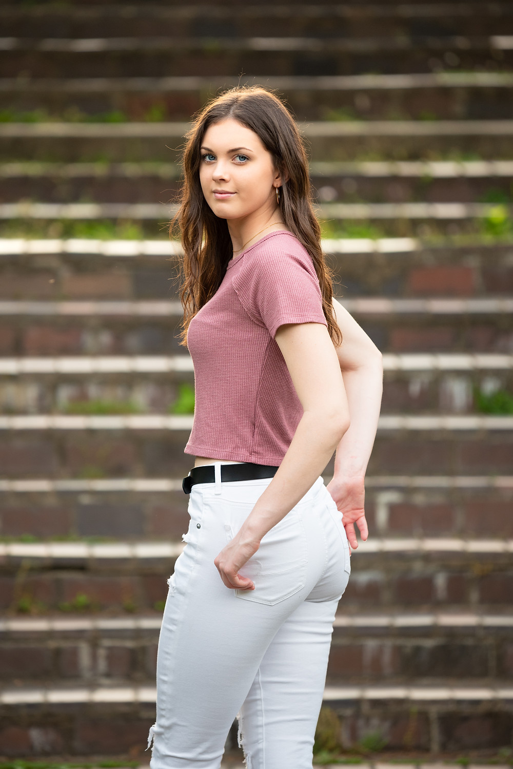 Senior girl posed looking back at the camera wearing a pink top and white jeans