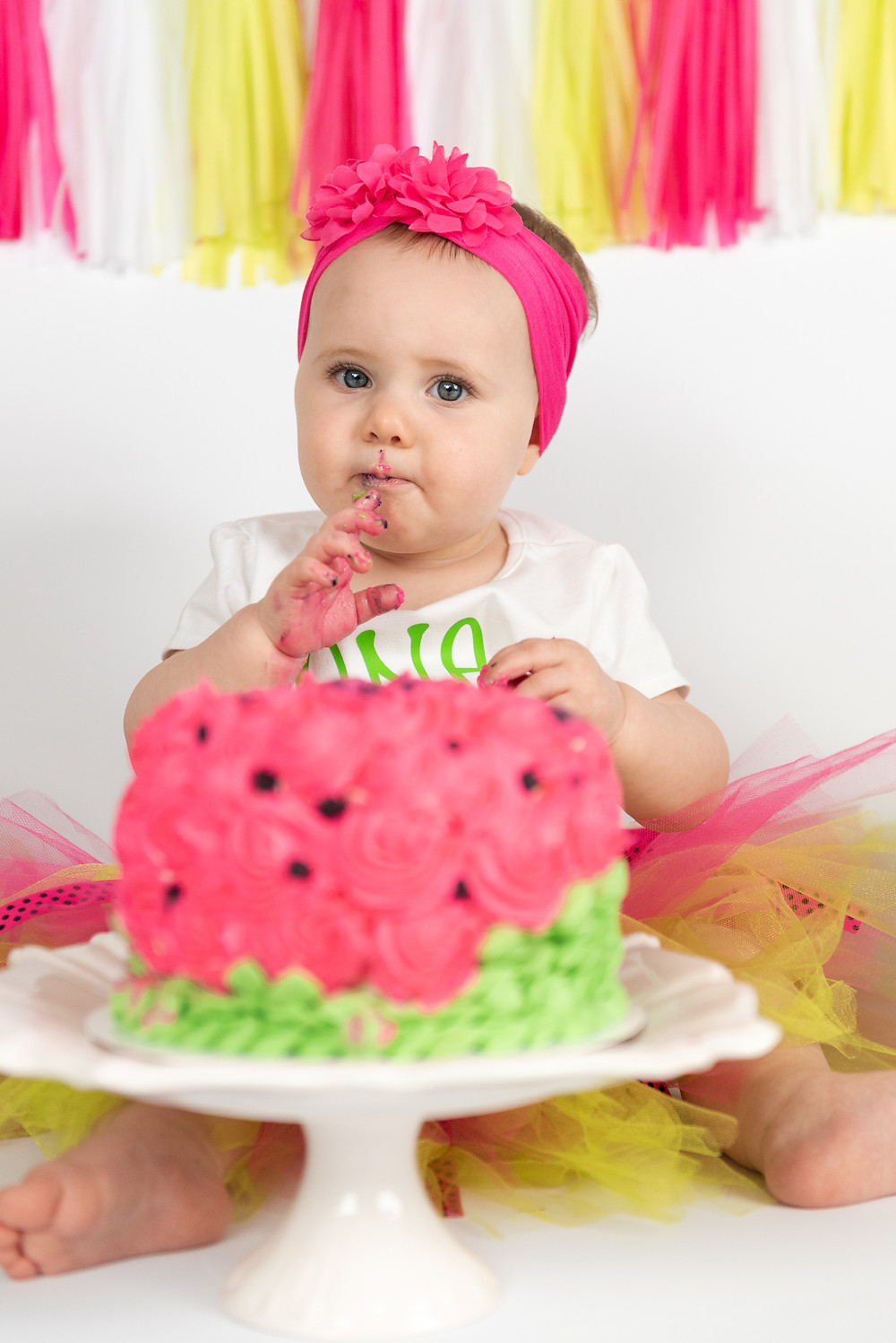 Baby girl getting messy during her watermelon themed cake smash photo session