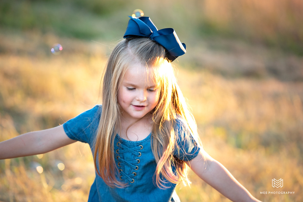 Photo of a girl with a blue bow in her hair playing with bubbles in a field near Pittsburgh