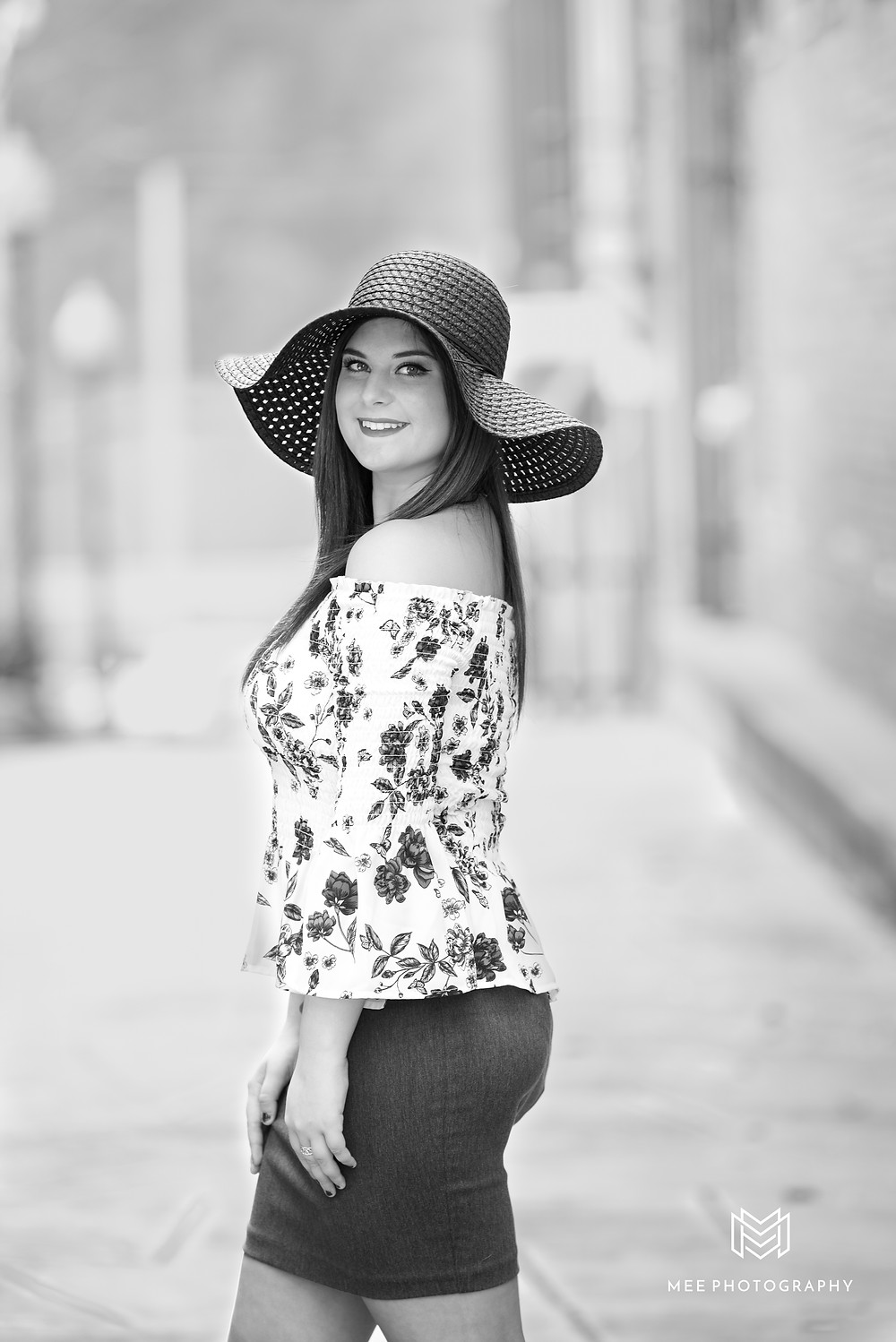 Black and white photo of a girl posing for her senior pictures wearing a black floppy hat.