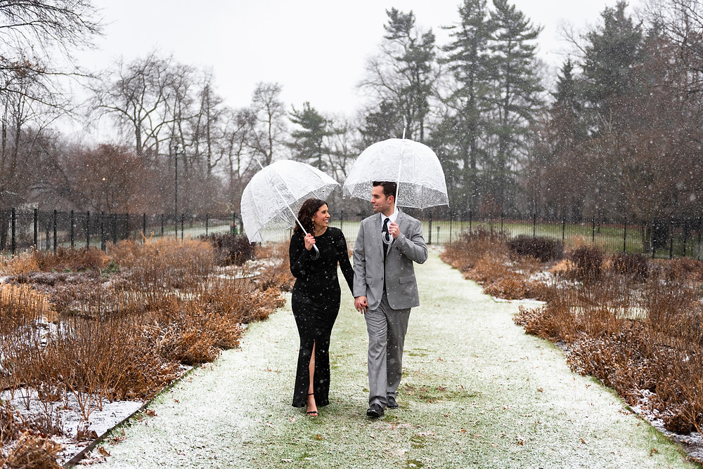 Engaged couple walking through the garden with umbrellas at Hartwood Acres in Allison Park, PA
