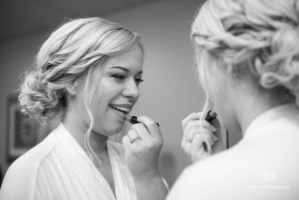 Black and white photo of bride putting on lipstick in mirror