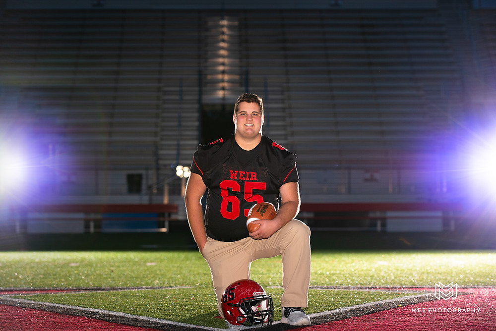 Senior guy creative football photos at night on the field with flashes