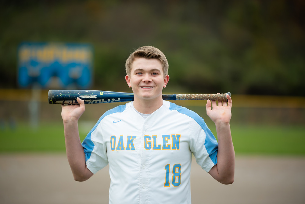 Senior guy standing in baseball field at Oak Glen High School holding a bat over his shoulders