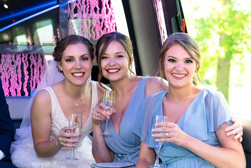 Bride and bridemaids drinking champagne on the party bus on the way to Lewis Family Farms