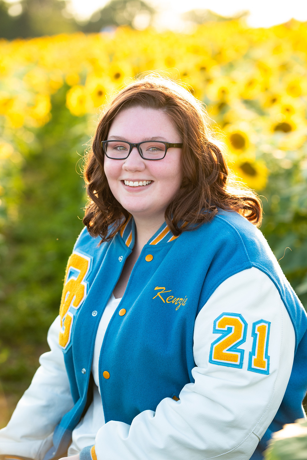 Senior girl photos in a letterman jacket in a sunflower field