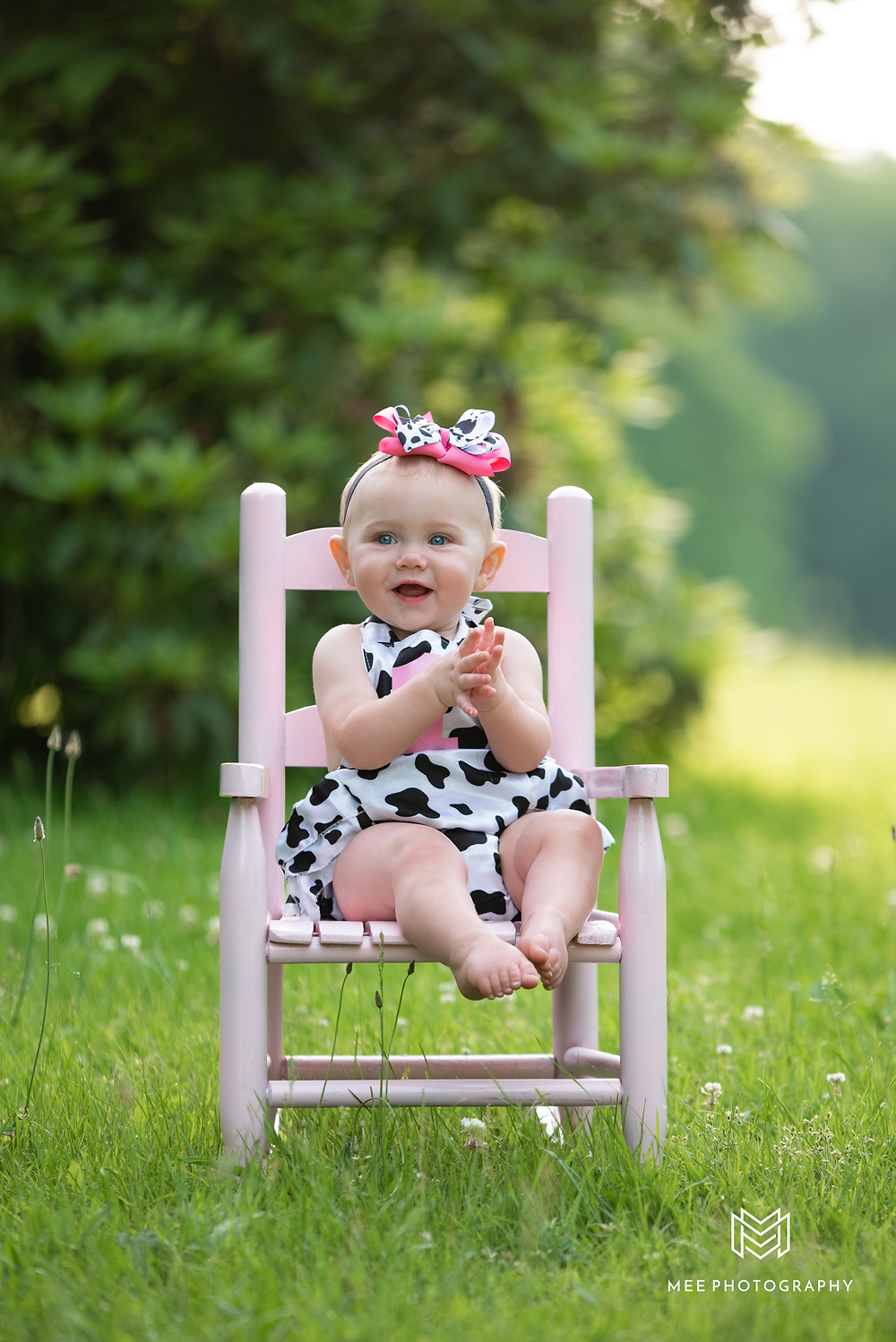Little girl in cow outfit sitting in a pink chair outside during her first birthday photos