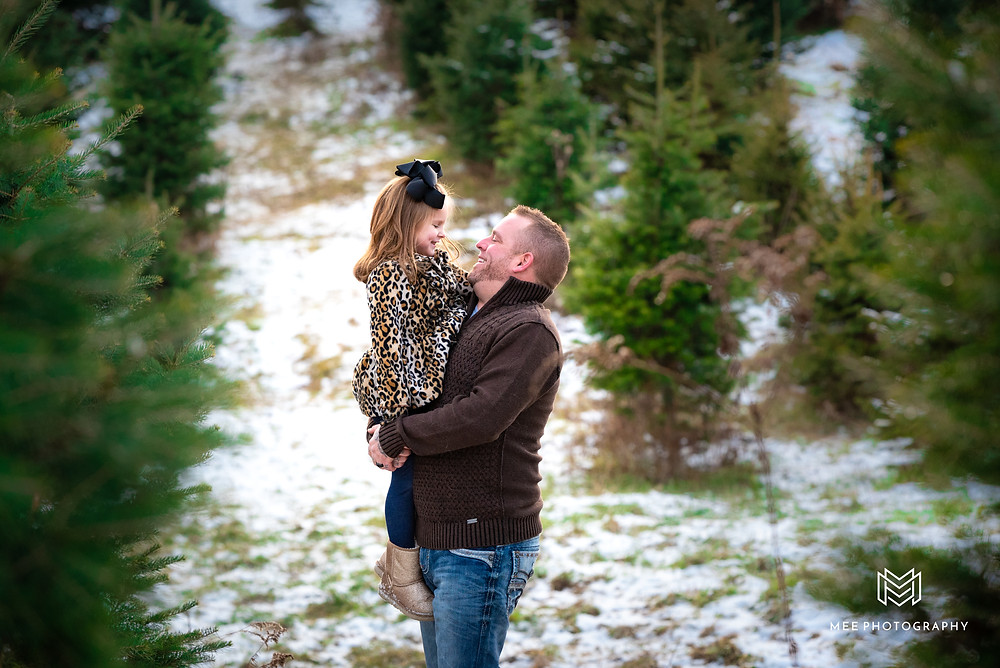 Dad holding his daughter during their Christmas photos at Windy Hill Tree Farm.