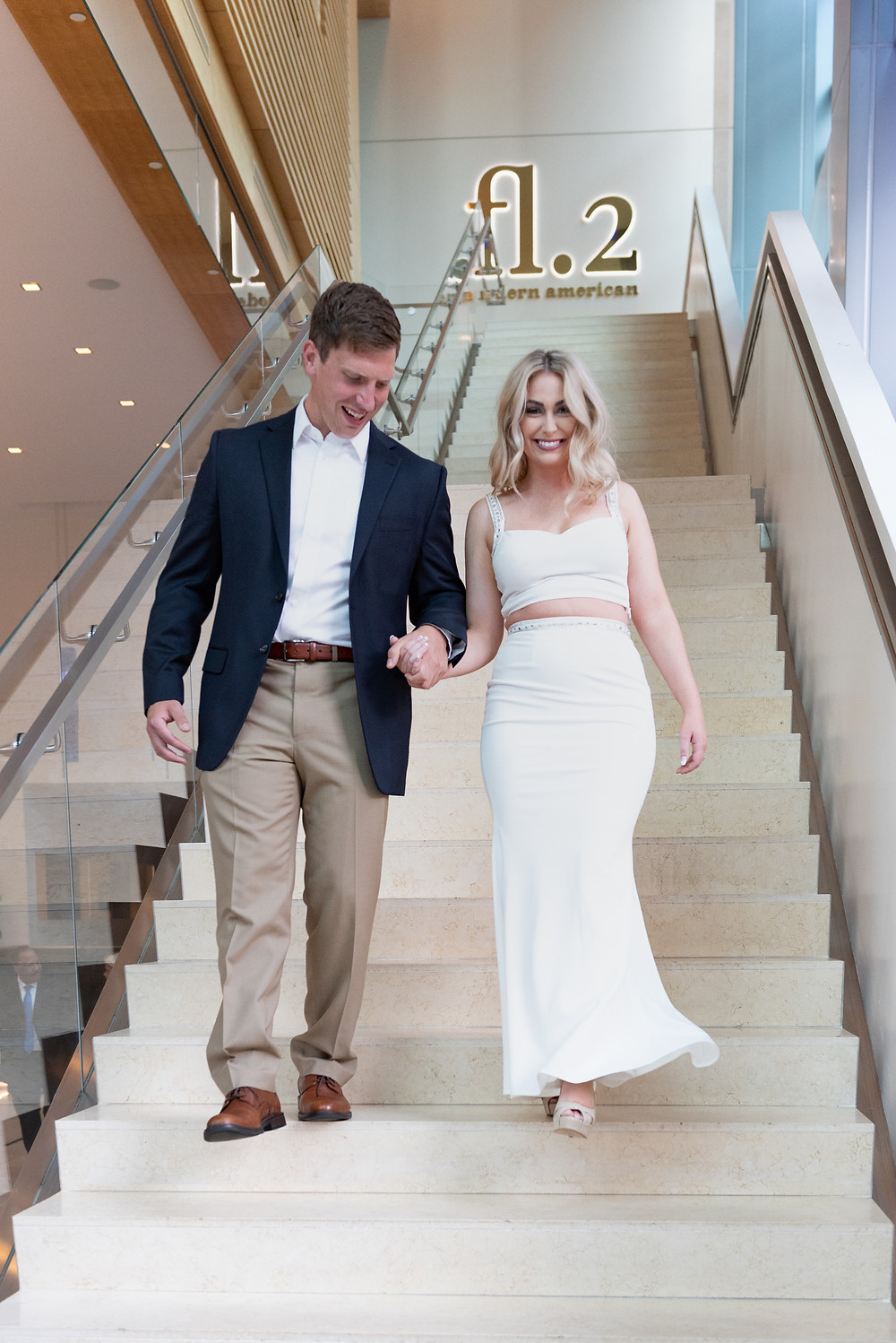 Couple walking down the foyer stairs at the Fairmont Hotel in Pittsburgh during their engagement shoot
