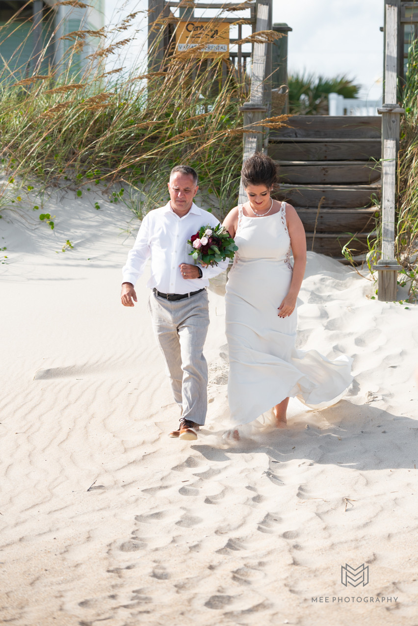 Bride and her dad walking down the aisle during their beach wedding
