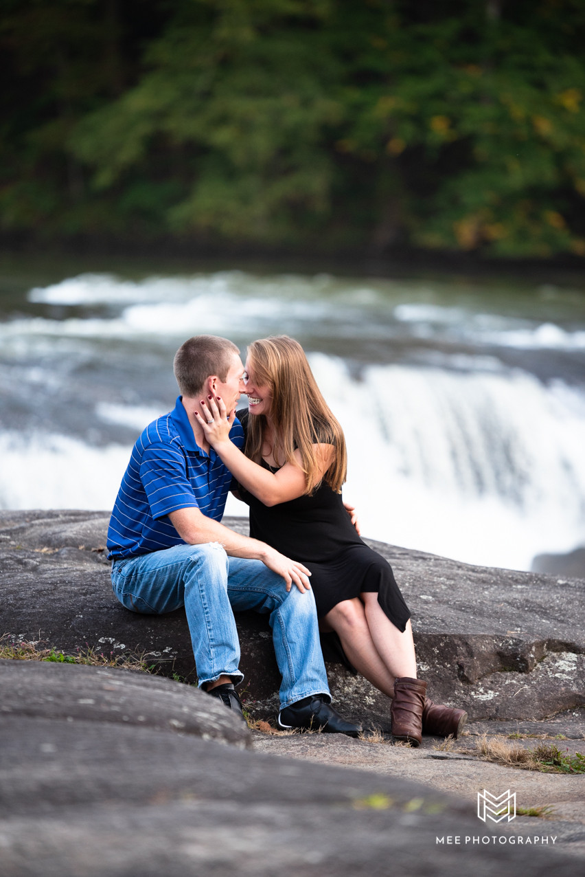 Couple laughing in front of waterfall in Farimont, West Virginia