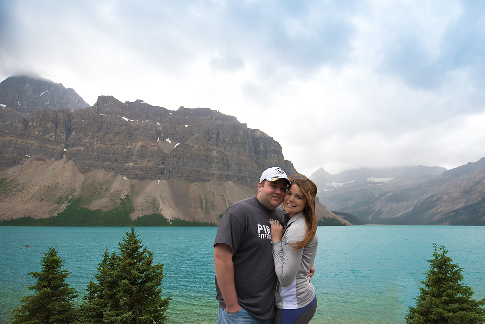 Photo of couple standing in front of Bow Lake in Alberta, Canada