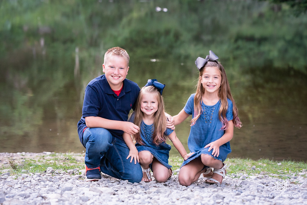 Three siblings posed in front of the lake at Tomlinson Run State Park