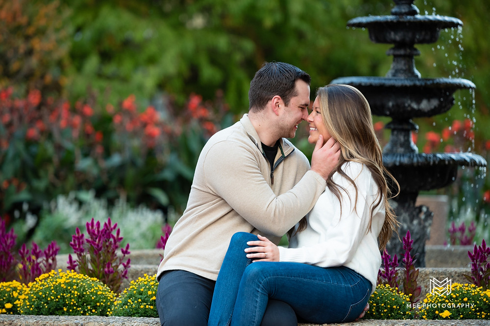 Oglebay engagement session with couple sitting in front of fountain