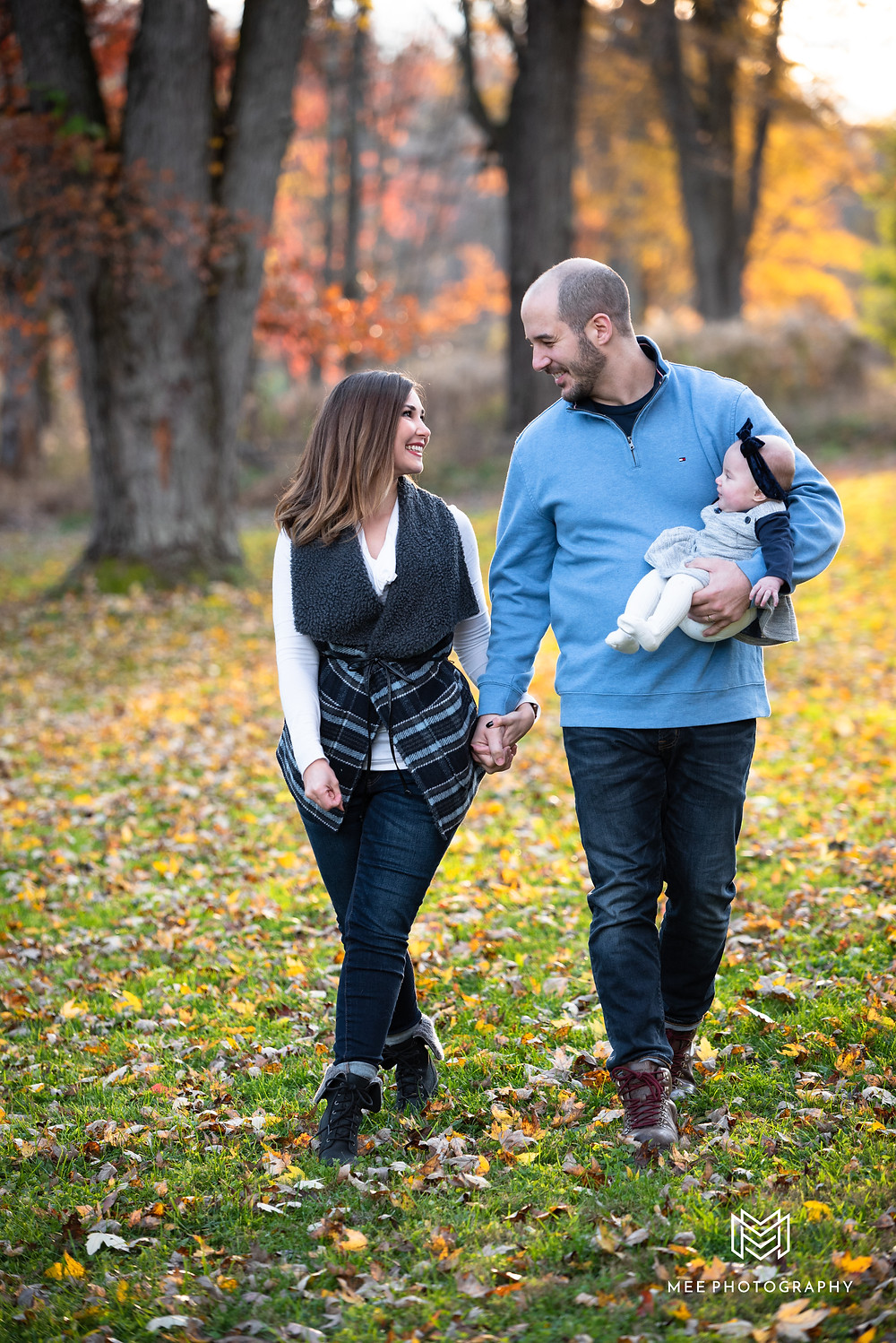 Parents walking and laughing with their baby during their photoshoot near Pittsburgh