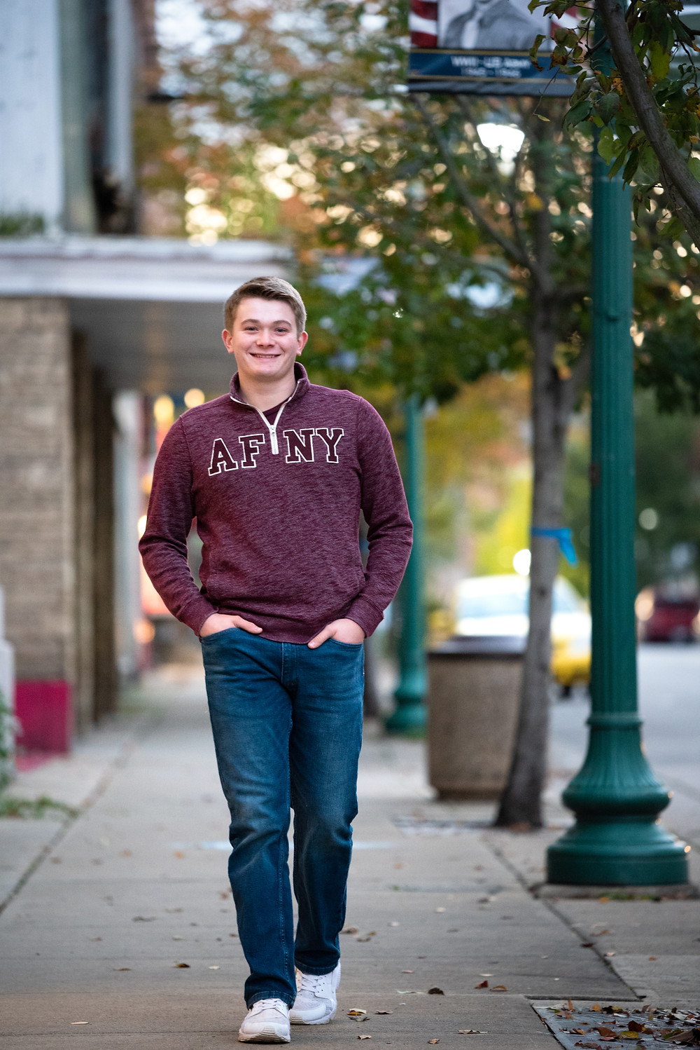 Senior guy strutting down the sidewalk during his photography session in East Liverpool, OH