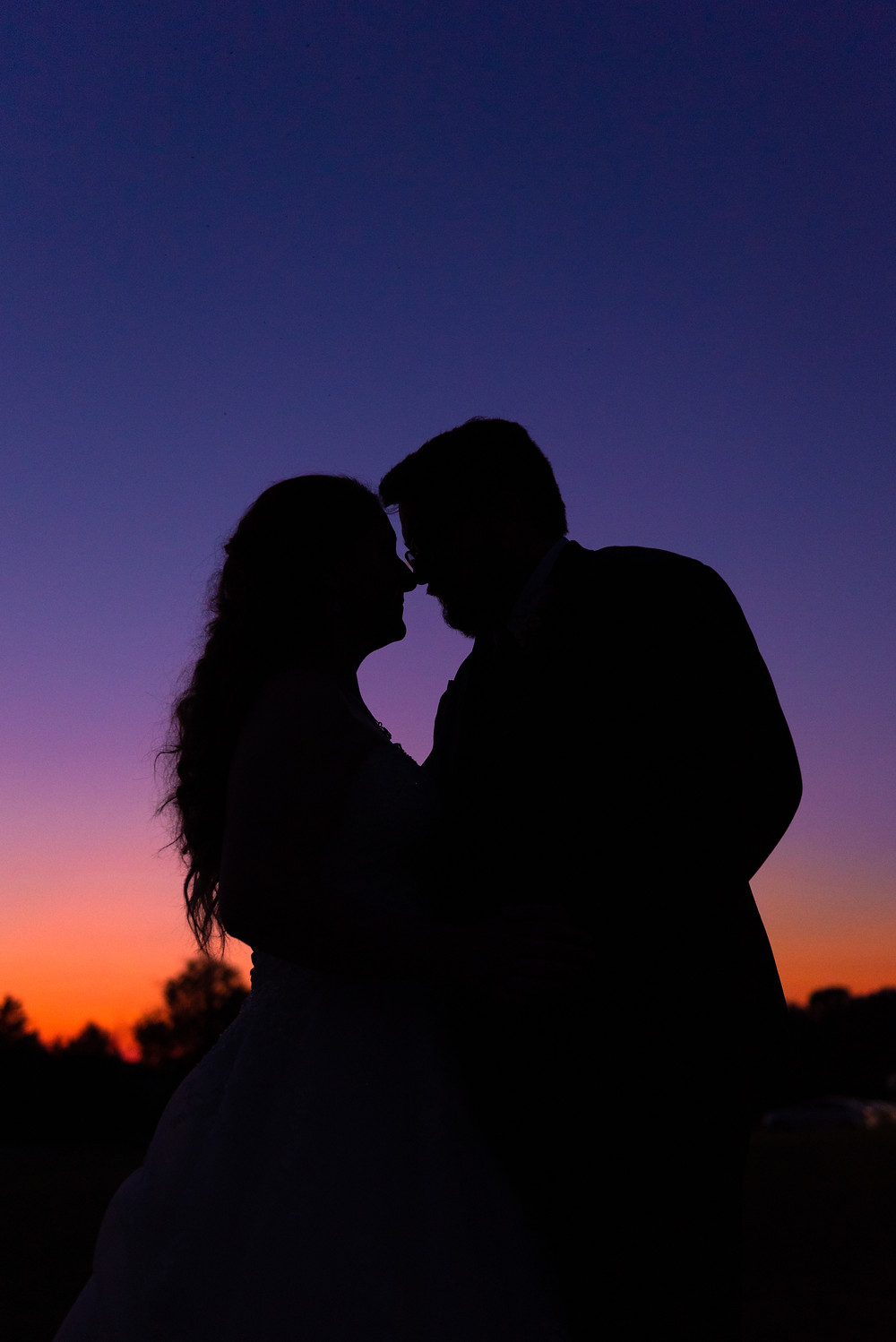 Sunset silhouette of bride and groom at drake's landing banquet center