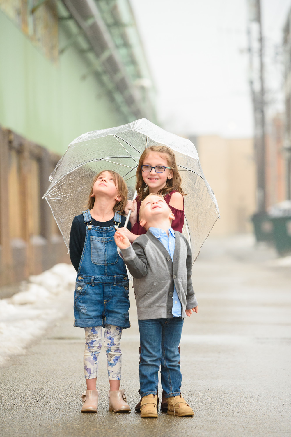 Three siblings laughing in the rain under a clear umbrella during their photo shoot in Weirton, Wv.
