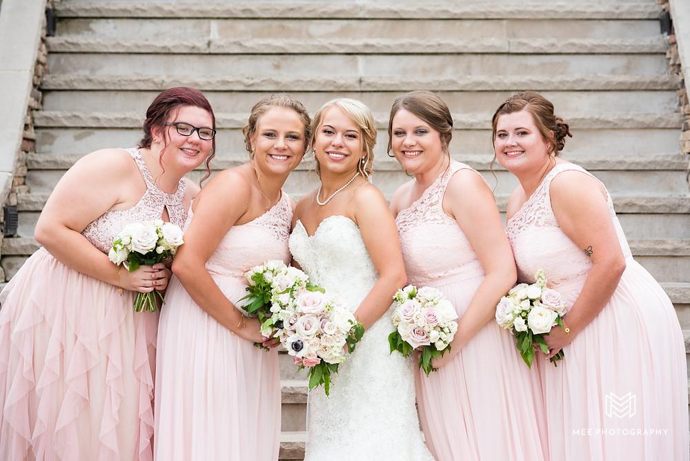 Bridesmaids posed smiling at the camera in blush dresses