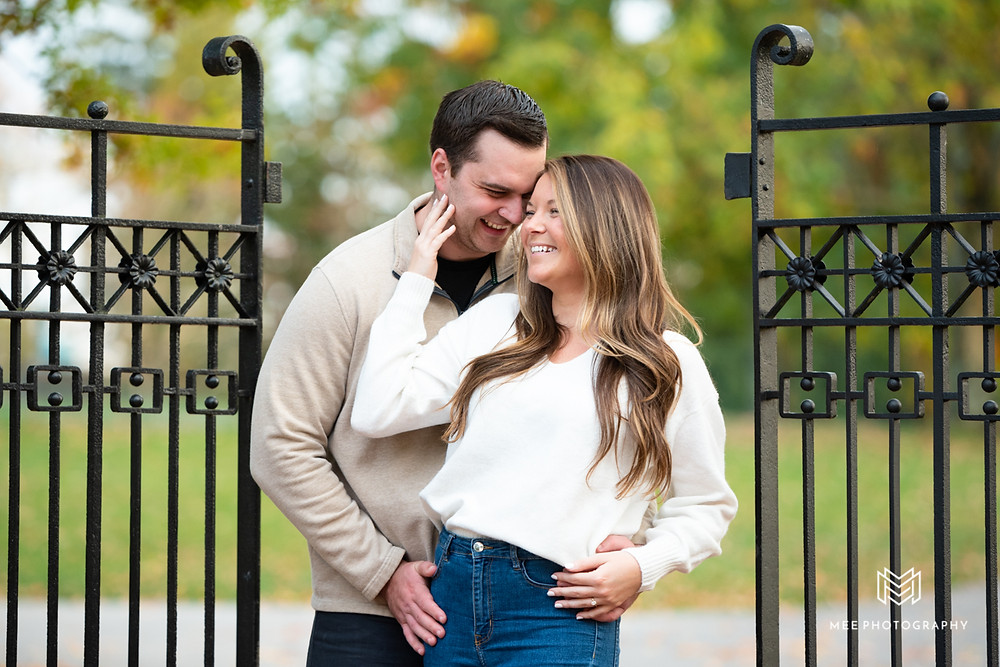 Couple wearing cream colored tops and jeans laughing during their Oglebay engagement photoshoot