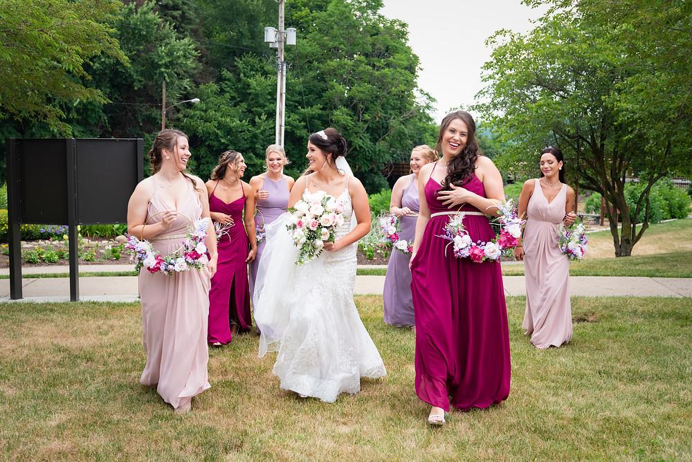 Bridesmaids wearing burgundy, mauve, and light pink dresses