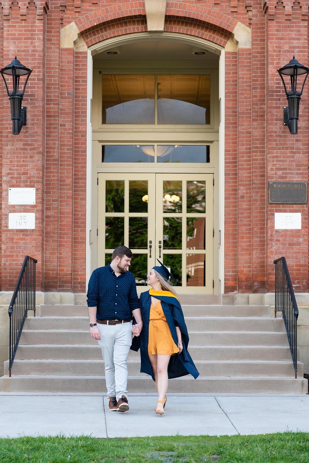 Couple walking and laughing during graduation photos at WVU