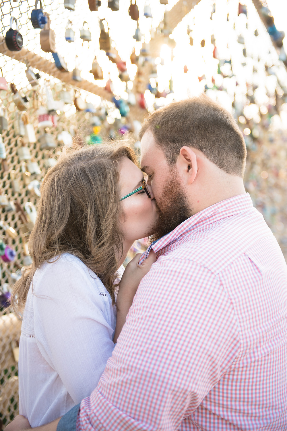 A couple kissing on a bridge with colorful locks and sunlight in the background