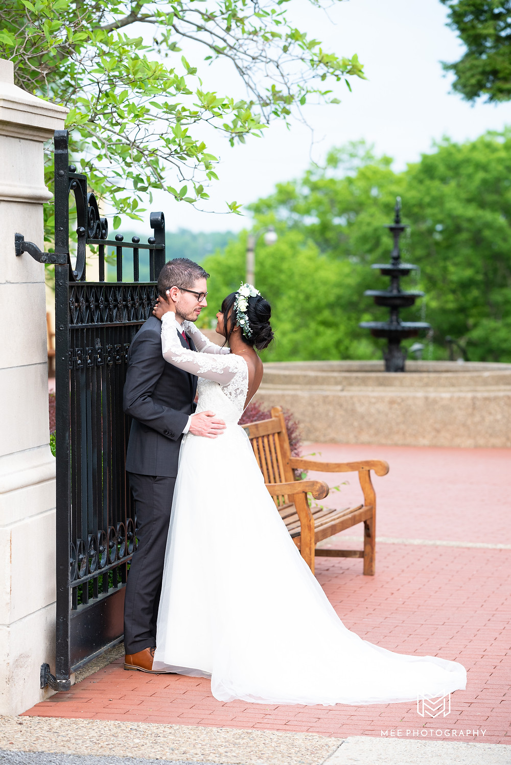 Bride and groom posed in front of iron gate with fountain in the background at Oglebay