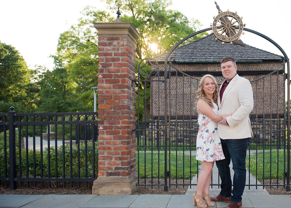 Newly engaged couple posed in front of building at Point State Park during their engagement session with MEE Photography