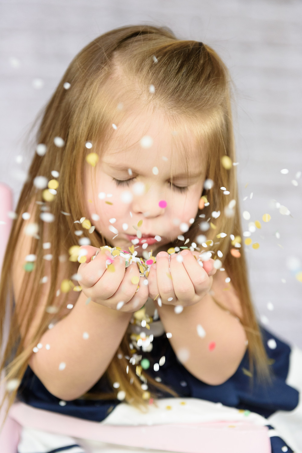 Girl blowing confetti during her birthday photo session near Pittsburgh.