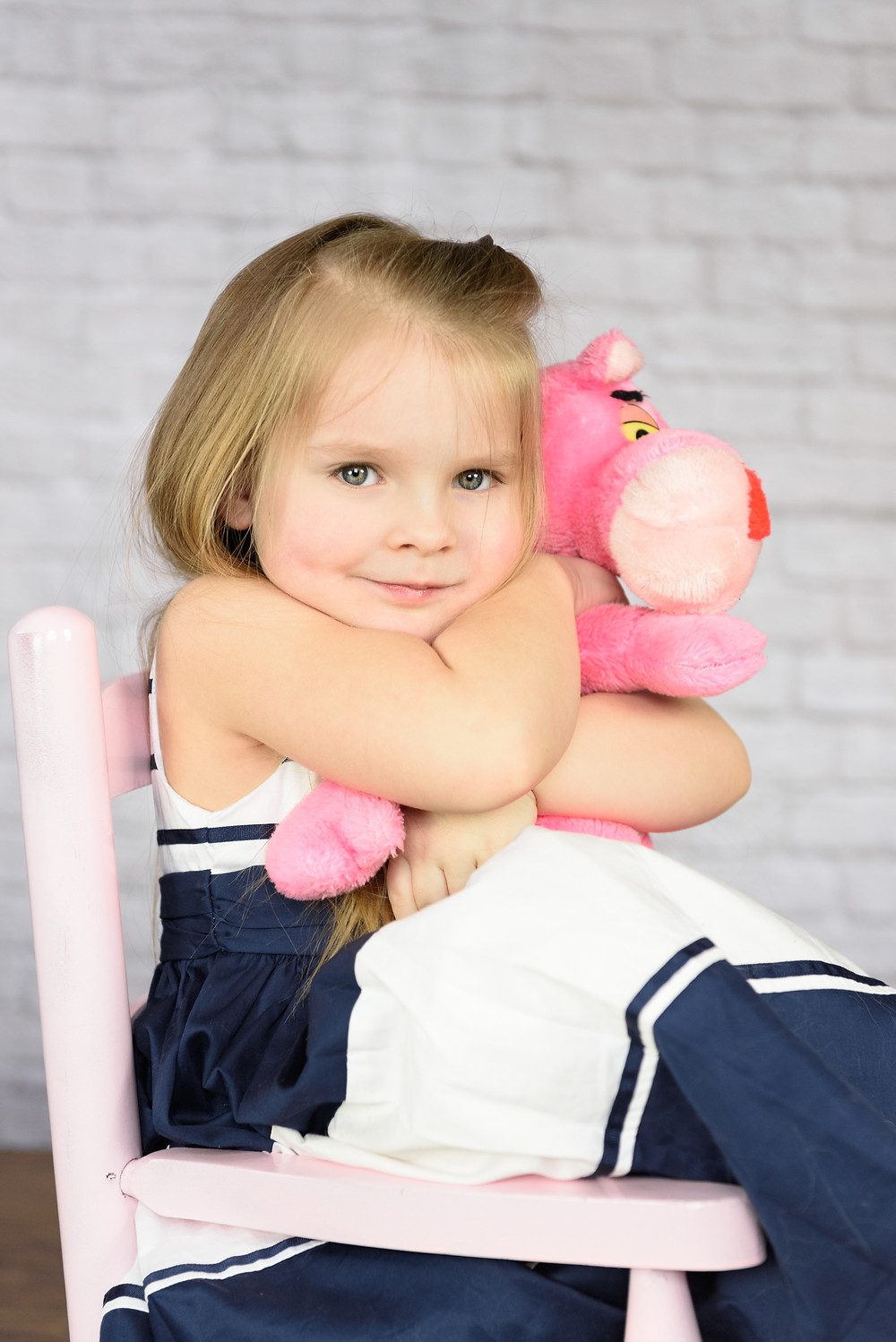 Girl sitting in a pink chair hugging her pink panther stuffed animal. There is a white brick backdrop behind her.