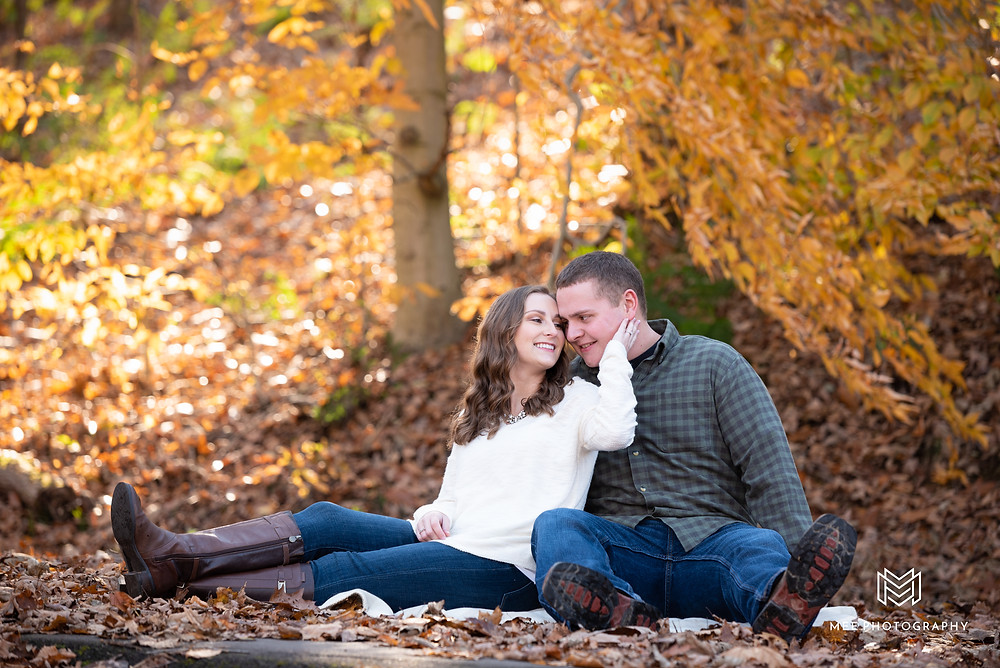Couple sitting in the fall leaves during their engagement photography session near Pittsburgh