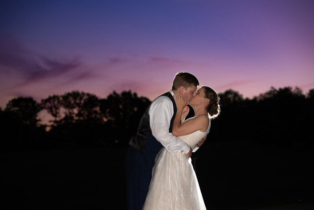 Bride and groom kiss at sunset with a pink sky at Lewis Family Farms near Pittsburgh