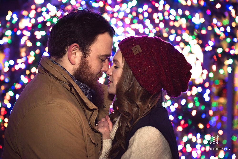 Christmas engagement session at Phipps Conservatory with multicolored lights behind the couple
