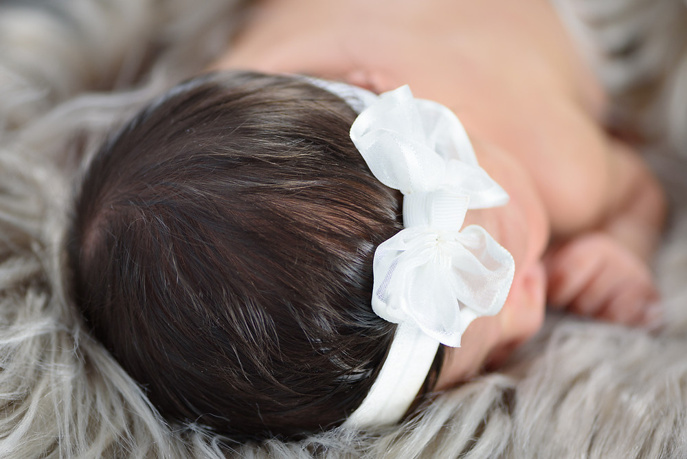 A detail shot of a newborn baby girl with a full head of black hair. Taken during her first photography session.