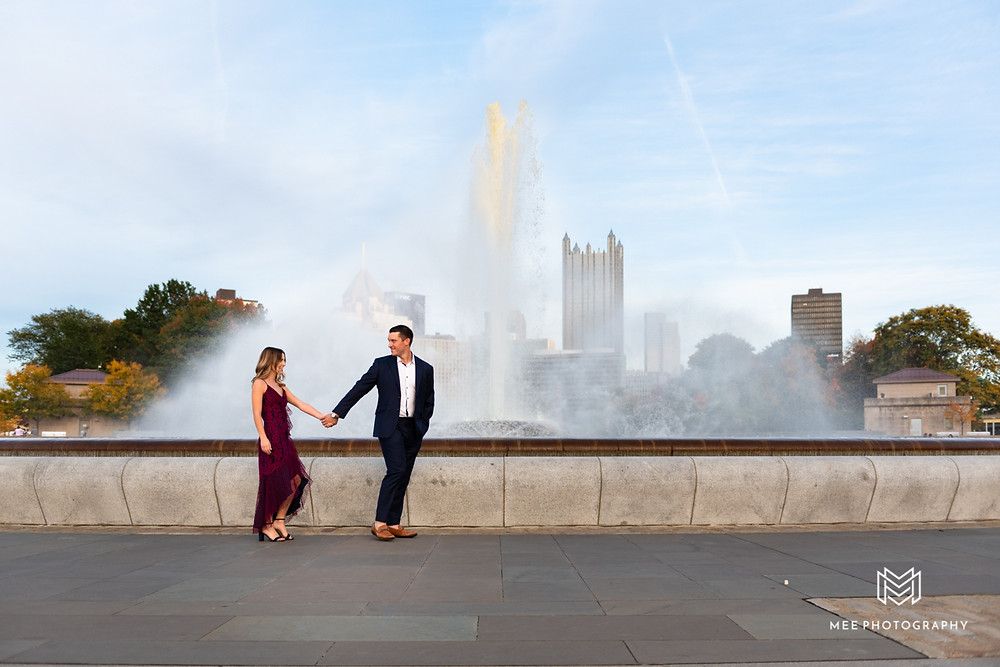 Couple walking and holding hands during Point State Park engagement session
