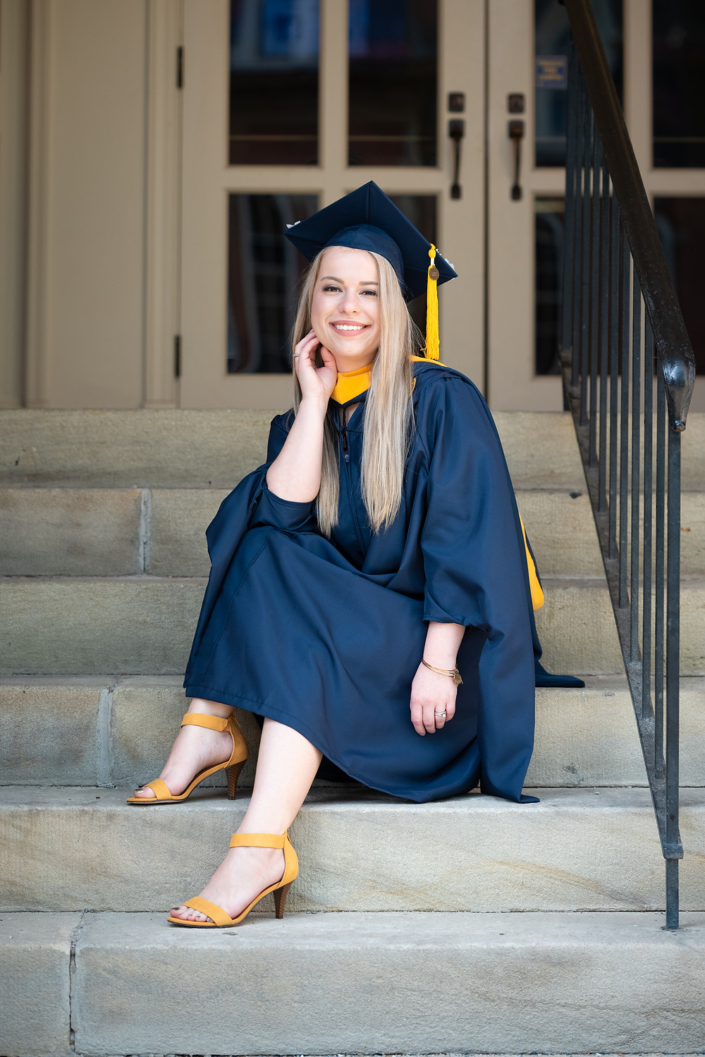 Girl sitting on steps at WVU in her graduation cap and gown